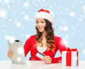 Woman with gift tablet pc and credit card christmas x mas online shopping concept in santa helper hat box computer Royalty Free Stock Photography