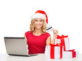 Woman with gifts laptop computer and credit card christmas x mas online shopping concept in santa helper hat gift boxes Royalty Free Stock Photo