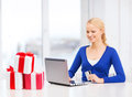 Woman with gifts laptop computer and credit card christmas x mas online shopping concept smiling gift boxes Stock Image