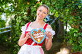 Woman with gingerbread hart in bavaria beergarden young traditional bavarian clothes or tracht a souvenir heart on oktoberfest Royalty Free Stock Photography