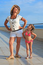Woman and girl do morning exercise on veranda Stock Photo