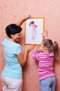 Woman with girl hanging up a picture Stock Photography