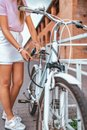 Woman girl standing in the park by bike. In the summer in the city, in a lock with a chain, unlocks puts on a bicycle Royalty Free Stock Photo
