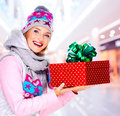 Woman gives the christmas gift photo of young adult dressed in a winter outerwear indoors Royalty Free Stock Photography