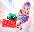 Woman gives the christmas gift photo of young adult dressed in a winter outerwear indoors Royalty Free Stock Images