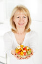 Woman gives fruit salad hands Royalty Free Stock Image