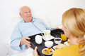 Woman giving breakfast to senior citizen in bed at home Royalty Free Stock Photo