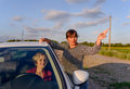 Woman giving directions to a female driver who has lost her way on rural road through fields of sunflowers pointing in the Royalty Free Stock Images