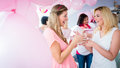 Woman giving gift to pregnant friend on baby shower Royalty Free Stock Photo