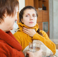Woman giving glass of water to unwell friend in home Stock Photography