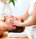 Woman giving happy man face massage Stock Image
