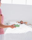 Woman giving a present to her husband in bed Stock Photos