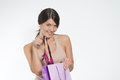 Woman giving a sneak peek at new lacy lingerie beautiful young lifting it out of the shopping bag with her finger while the Stock Photography
