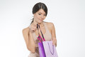 Woman giving a sneak peek at new lacy lingerie beautiful young lifting it out of the shopping bag with her finger Royalty Free Stock Image