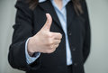 Woman giving thumbs up professional in business suit in approval on grey background Royalty Free Stock Photography