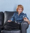 Woman with a glass brandy on couch Stock Photos