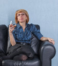 Woman with a glass brandy on couch Stock Image