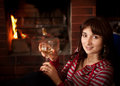 Woman with a glass of wine near the fireplace Stock Image