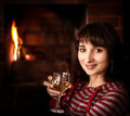 Woman with a glass of wine near the fireplace Stock Images