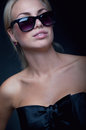 Woman in glasses beautiful young blond model wearing stylish top with a silk band black sun tender pink lipstick gloss smiling Royalty Free Stock Photos