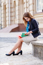 Woman in glasses sits on a stone bench and reading a book Royalty Free Stock Photo