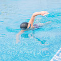 Woman in goggles swimming front crawl style young girl and cap stroke the blue water pool Royalty Free Stock Image