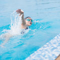 Woman in goggles swimming front crawl style young girl and cap stroke the blue water pool Royalty Free Stock Photos