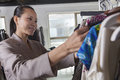 Woman going through clothes at fashion store Royalty Free Stock Photo