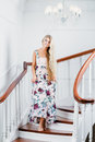 Woman going down the stairs portrait of young attractive in a long dress Stock Image