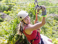 Woman going on a jungle zipline adventure smiles while enjoying fun zip line tour in the while vacation Royalty Free Stock Image