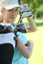 Woman with golf clubs carrying her Stock Photos
