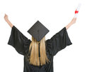 Woman in graduation gown rejoicing success rear view Royalty Free Stock Photography