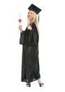 Woman in graduation gown showing diploma full length portrait of young and thumbs up Royalty Free Stock Photo