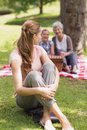 Woman with grandmother and granddaughter in background at park portrait of a smiling women the Royalty Free Stock Photography