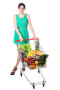 Woman in green dress with full shopping grocery cart teen girl a supermarket trolley of groceries of food Royalty Free Stock Photography