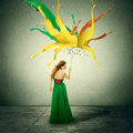 Woman in green dress with umbrella as shelter against colorful drops splashes of paint falling down Royalty Free Stock Photo