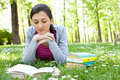 Woman on green field and reading Stock Image