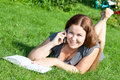 Woman on green grass reading book and speaking on phone in summer Stock Image