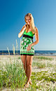 Woman in green sundress happy on a beach Stock Photography