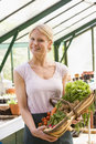 Woman in greenhouse holding basket of vegetables Royalty Free Stock Images