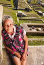 Woman grieves at the cemetery old homeless african lady sitting on wall in front of Stock Photography