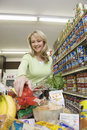 Woman with grocery shopping in supermarket smiling blond women Stock Images