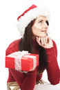 Woman guessing the contents of her xmas gift christmas in a decorative red box sitting with chin on hand looking upwards in Stock Photos