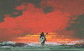 Woman with guitar on back standing in the sea at sunset