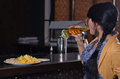 Woman gulping down a beer at the bar view from behind of young pint during happy hour with plate of snacks counter in front her Stock Image