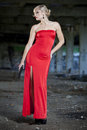 Woman with gun in red dress young vintage look holding a handgun old fabric ruins Stock Photos