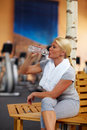 Woman in gym drinking water Stock Photography