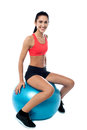 Woman in gym exercising with pilates ball smiling fit sitting on fitness Stock Images