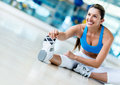Woman at the gym fit stretching her leg and smiling Royalty Free Stock Photography