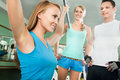 Woman at the gym fitness doing arms exercises on a machine Stock Image